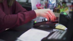 Το θηλυκό χέρι κρατά μια πιστωτική κάρτα πέρα από το τερματικό φιλμ μικρού μήκους