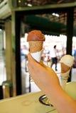 Το θηλυκό χέρι κρατά το παγωτό στη γωνία βάφλα πάγου κρέμας κώνων Ψυγείο με το παγωτό στο υπόβαθρο Στοκ Φωτογραφίες