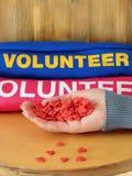 Το θηλυκό χέρι κρατά πολλές μικρές καρδιές Εθελοντής ομοιόμορφος στο υπόβαθρο να προσφερθεί εθελοντικά την έννοια Στοκ εικόνες με δικαίωμα ελεύθερης χρήσης
