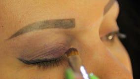 Το θηλυκό χέρι με μια βούρτσα κάνει το μάτι makeup με τις σκοτεινές πορφυρές σκιές απόθεμα βίντεο