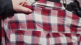 Το θηλυκό χέρι παίρνει ένα πουκάμισο καρό από την κρεμάστρα στο σύγχρονο κατάστημα απόθεμα βίντεο