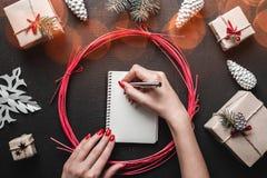 Το θηλυκό χέρι που γράφει μια επιστολή σε Santa στο σκοτεινό υπόβαθρο με τα δώρα Χριστουγέννων, έλατο διακλαδίζεται, κώνοι πεύκων Στοκ Φωτογραφίες
