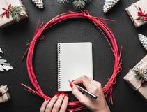 Το θηλυκό χέρι που γράφει μια επιστολή στο μαύρο υπόβαθρο με τα δώρα Χριστουγέννων, έλατο διακλαδίζεται, κώνοι πεύκων και διακοσμ Στοκ εικόνες με δικαίωμα ελεύθερης χρήσης