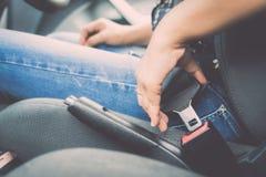 Το θηλυκό χέρι ` s στερεώνει τη ζώνη ασφαλείας του αυτοκινήτου Στοκ εικόνα με δικαίωμα ελεύθερης χρήσης