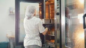 Το θηλυκό ψήνει στην εμπορική κουζίνα - τραβά το ψωμί από το φούρνο φιλμ μικρού μήκους