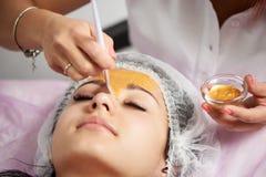 Το θηλυκό cosmetologist εφαρμόζει τη χρυσή μάσκα σε μια νέα γυναίκα σε ένα σαλόνι ομορφιάς Στοκ Εικόνες
