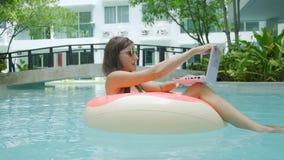Το θηλυκό freelancer κάθεται σε έναν διογκώσιμο κύκλο στη λίμνη και ρίχνει το lap-top στο νερό Πολυάσχολος κατά τη διάρκεια απόθεμα βίντεο
