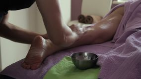 Το θηλυκό massagist ζυμώνει εντατικά το μόσχο στο αριστερό πόδι της κυρίας με το πετρέλαιο και τις πέτρες φιλμ μικρού μήκους
