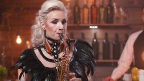 Το θηλυκό saxophonist τζαζ αποδίδει μπροστά από έναν μετρητή φραγμών απόθεμα βίντεο