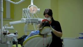 Το θηλυκό stomatologist γιατρών στην εργασία μεταχειρίζεται και λευκαίνει τα δόντια στο νέο ασθενή γυναικών στην ιατρική οδοντική φιλμ μικρού μήκους