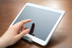 Το θηλυκό δάχτυλο αγγίζει μια κενή άσπρη επιχειρησιακή ταμπλέτα σε έναν κάτοχο σε ένα γραφείο Στοκ φωτογραφίες με δικαίωμα ελεύθερης χρήσης