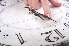 Το θηλυκό δάχτυλο αλλάζει το χρόνο σε ένα ρολόι Στοκ Φωτογραφίες