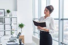 Το θηλυκό γράψιμο εργαζομένων γραφείων σημειώνουν κάτω και το σχέδιο ημέρας στο σημειωματάριό της, που στέκεται στον εργασιακό χώ στοκ φωτογραφίες