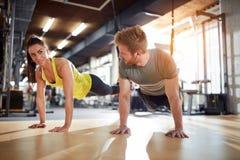 Το θηλυκό και το αρσενικό που κάνουν τις ασκήσεις για ενισχύουν τα χέρια Στοκ Φωτογραφία