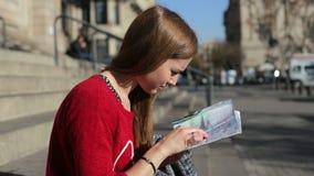 Το θηλυκό στα σκαλοπάτια βλέπει το χάρτη τουριστών γύρω από την κυκλοφορία πίσω απόθεμα βίντεο