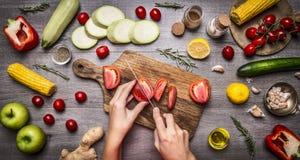 Το θηλυκό χέρι έκοψε τις ντομάτες στο αγροτικό γκρίζο υπόβαθρο, γύρω από τα συστατικά ποικιλίας ψέματος, τα λαχανικά, τα φρούτα,  Στοκ Εικόνες