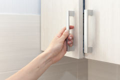 Το θηλυκό χέρι ανοίγει τις πόρτες ντουλαπιών, κλείνει επάνω Στοκ Εικόνες