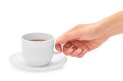Το θηλυκό χέρι κρατά ένα φλυτζάνι του τσαγιού η ανασκόπηση απομόνωσε το λευκό στοκ εικόνες