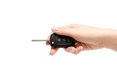 Το θηλυκό χέρι κρατά τα κλειδιά αυτοκινήτων στο άσπρο υπόβαθρο στοκ εικόνα