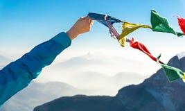 Το θηλυκό χέρι κρατά τις χρωματισμένες σημαίες Ευτυχής επιτυχία που φθάνει στην κορυφή βουνών Στοκ Εικόνα