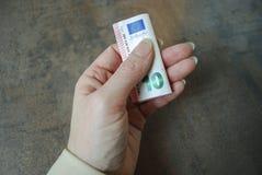 Το θηλυκό χέρι κρατά το διπλωμένο τραπεζογραμμάτιο νομίσματος Στοκ φωτογραφία με δικαίωμα ελεύθερης χρήσης