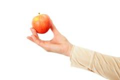 Το θηλυκό χέρι προσφέρει να πάρει το κόκκινο μήλο Στοκ Φωτογραφία