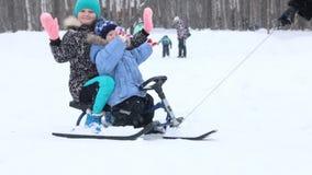 Το θηλυκό χέρι σέρνει το ευτυχή αγόρι και το κορίτσι στο έλκηθρο πλησίον κατά τη διάρκεια των χιονοπτώσεων στο χειμερινό πάρκο φιλμ μικρού μήκους