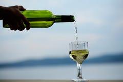Το θηλυκό χέρι χύνει το κρασί Στοκ Φωτογραφίες