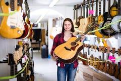 Το θηλυκό 14-19 χρονών αποφασίζει σχετικά με την ακουστική κιθάρα Στοκ Εικόνες