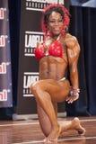 Το θηλυκό bodybuilder στο κόκκινο μπικίνι παρουσιάζει μεγάλα triceps της Στοκ φωτογραφίες με δικαίωμα ελεύθερης χρήσης