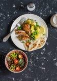 Το θυμάρι λεμονιών έψησε το κοτόπουλο, βρασμένες πατάτες με τα πράσινα μπιζέλια, σαλάτα με τις φακές και τις ντομάτες σε ένα σκοτ Στοκ εικόνα με δικαίωμα ελεύθερης χρήσης