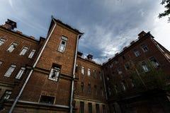 Το θλιβερό και εγκαταλειμμένο νοσοκομείο ή ένα σπίτι με τα σπασμένους παράθυρα και contrastingà τον ουρανό 'Στοκ Εικόνες