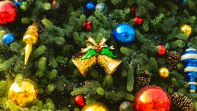 Το διακοσμημένο χριστουγεννιάτικο δέντρο με τη ζωηρόχρωμη σφαίρα Χριστουγέννων και το χρυσό κουδούνι εξωραΐζουν Στοκ Φωτογραφία
