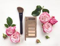 Το διακοσμητικό επίπεδο βάζει τη σύνθεση με τα καλλυντικά και τα λουλούδια στο άσπρο υπόβαθρο Στοκ φωτογραφία με δικαίωμα ελεύθερης χρήσης