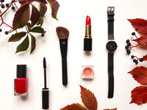 Το διακοσμητικό επίπεδο βάζει τη σύνθεση με τα καλλυντικά, τα εξαρτήματα γυναικών και τα φύλλα και τα μούρα φθινοπώρου Επίπεδος β Στοκ Φωτογραφίες