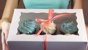 Το διακοσμητικό κιβώτιο δώρων έδεσε με τα cupcakes μια τυρκουάζ κορδέλλα στα θηλυκά χέρια απόθεμα βίντεο