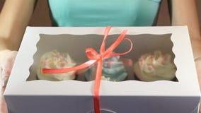 Το διακοσμητικό κιβώτιο δώρων έδεσε με τα cupcakes μια τυρκουάζ κορδέλλα στα θηλυκά χέρια φιλμ μικρού μήκους
