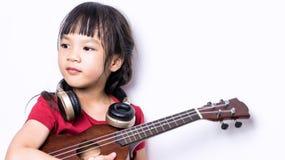 Το ιαπωνικό κορίτσι παίζει την κιθάρα και φορά το ακουστικό Στοκ Φωτογραφία