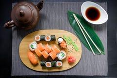 Το ιαπωνικό σούσι κυλά, σάλτσα σόγιας, πιπερόριζα και chopsticks στο σκοτεινό υπόβαθρο Τοπ όψη Επίπεδος βάλτε Στοκ Εικόνα
