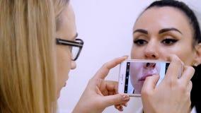 Το ιατρικό γραφείο, ένας θηλυκός γιατρός στα γυαλιά, κάνει τις φωτογραφίες των υπομονετικών χειλιών ` s, στο τηλέφωνο, μετά από τ απόθεμα βίντεο