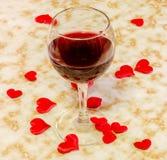 Το διαφανές γυαλί με το κόκκινο κρασί και τις υφαντικές κόκκινες καρδιές βαλεντίνων, παλαιό υπόβαθρο εγγράφου, κλείνει επάνω στοκ φωτογραφίες με δικαίωμα ελεύθερης χρήσης