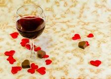 Το διαφανές γυαλί με το κόκκινο κρασί, τη σοκολάτα καρδιών και τις υφαντικές κόκκινες καρδιές βαλεντίνων, παλαιό υπόβαθρο εγγράφο στοκ φωτογραφίες