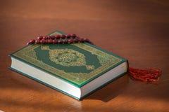 Το ιερό βιβλίο Quran και rosary Αραβικά γράφονται - μετάφραση - αποκαλούμενη Quran στοκ εικόνα