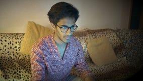 Το ινδικό άτομο στα γυαλιά κάθεται στο σπίτι στον καναπέ και εργάζεται για το lap-top απόθεμα βίντεο