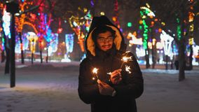 Το ινδικό άτομο στα γυαλιά κρατά τα φω'τα της Βεγγάλης και χαμογελά το βράδυ στο πάρκο φιλμ μικρού μήκους