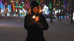 Το ινδικό άτομο στα γυαλιά κρατά τα φω'τα της Βεγγάλης στο πάρκο νύχτας απόθεμα βίντεο