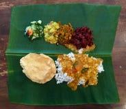 Το ινδικό ρύζι με την ποικιλία των πιάτων λαχανικών εξυπηρέτησε στο φρέσκο μεγάλο φύλλο μπανανών Στοκ Εικόνα