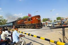 Το ινδικό τραίνο σιδηροδρόμων περνά ένα πέρασμα σιδηροδρόμου στοκ εικόνα με δικαίωμα ελεύθερης χρήσης