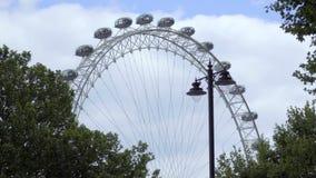 Το ιπποδρόμιο ματιών του Λονδίνου που υψώνεται πέρα από τα δέντρα απόθεμα βίντεο