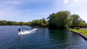 Το ιπτάμενο Jetlev, αθλητής, αθλητικός τύπος πετά πέρα από τη λίμνη και εκτελεί τις ακροβατικές επιδείξεις απόθεμα βίντεο